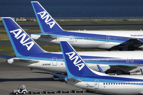 An All Nippon Airways Co. (ANA) aircraft, top, taxis on the tarmac past other parked ANA aircraft at Haneda Airport in Tokyo, Japan, on Sunday, Oct. 27, 2013. ANA Holdings Inc., the parent company of All Nippon Airways, is scheduled to announce first-half earnings on Oct. 30. Photographer: Kiyoshi Ota/Bloomberg