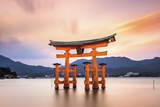 Miyajima, Hiroshima, Japan at the great gate of Itsukushima shrine. (gate sign reads Itsukushima Shrine)